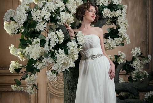 Smiling bride near the tree with white flowers.