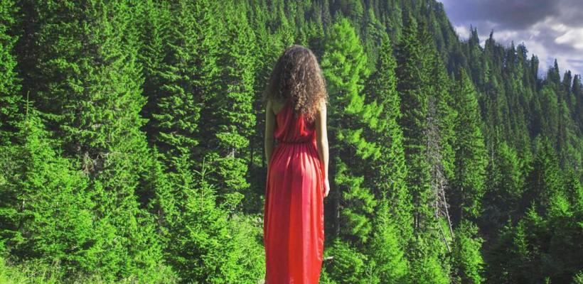 O româncă îmbrăcată în roșu e fotografiată pe fundalul unor locuri splendide din România