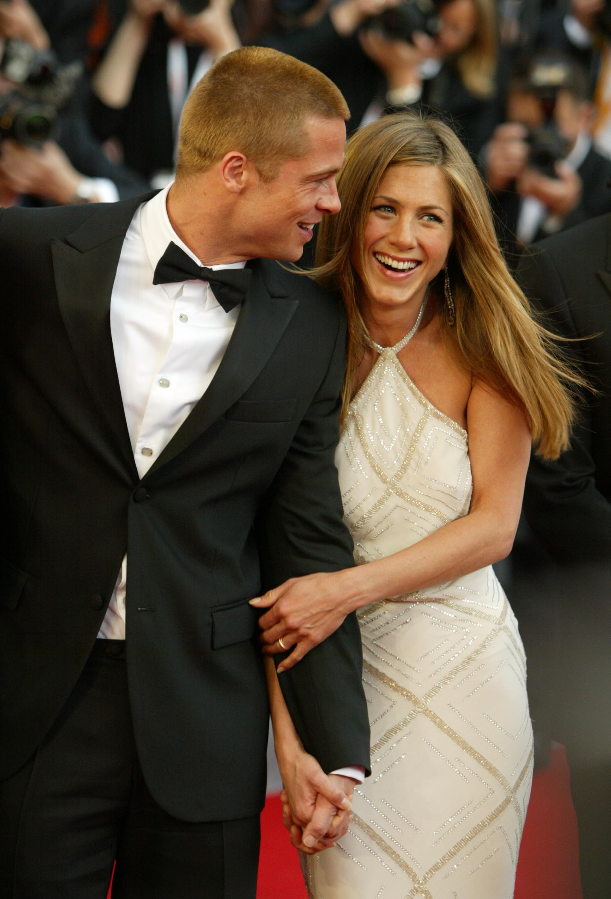 "CANNES, FRANCE - MAY 13: Actors Brad Pitt and Jennifer Aniston attend the World Premiere of epic movie ""Troy"" at Le Palais de Festival on May 13, 2004 in Cannes, France. Aniston wears a dress by Versace. (Photo by Dave Hogan/Getty Images)"