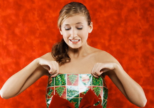 Woman Trying on Wrapping Paper Christmas Dress --- Image by © Beathan/Corbis