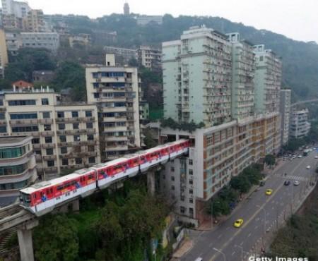 Într-un oraș din China, trenurile trec printr-un bloc de locuit de 19 etaje. O stație e amenajată în mijlocul turnului