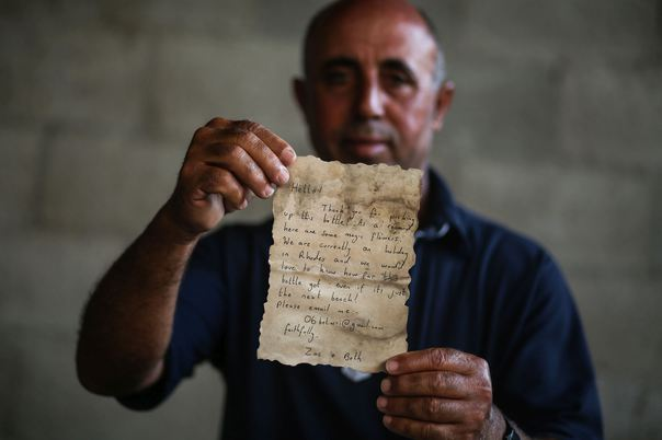 GAZA CITY, GAZA - AUGUST 22: A Palestinian fisherman Jihad al-Soltan displays a letter after he found it in a bottle off a Gaza beach, containing a message which was written and thrown to the sea from Greece's Rhodes Island by 2 British citizen when they were on holiday, in Gaza city, Gaza on August 22, 2017. Ali Jadallah / Anadolu Agency
