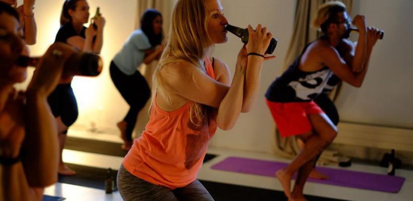 Oamenii beau bere rece în Londra, în timp ce fac Yoga